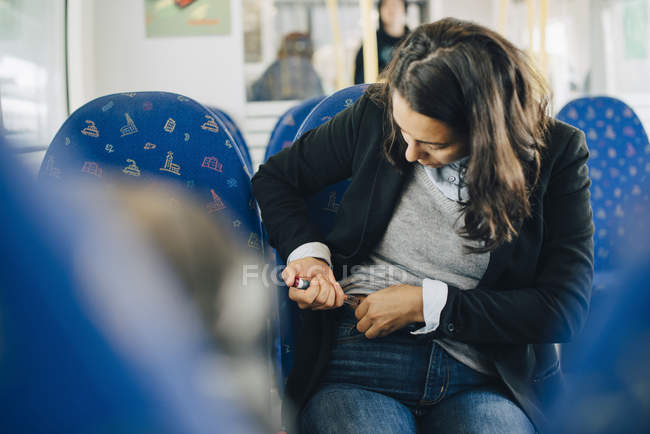 Жінка ін'єкційні в живіт, сидячи біля вікна в поїзді — стокове фото
