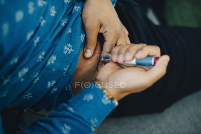 Mittelteil des Geschäftsmannes spritzt Insulin in den Bauch, während er auf dem Sofa sitzt — Stockfoto