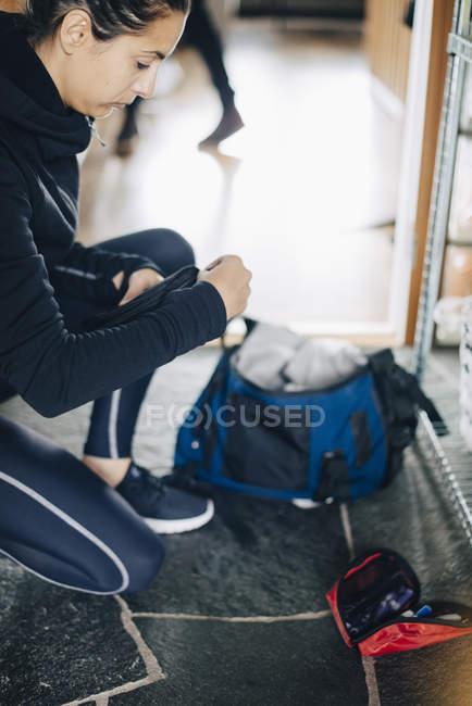 Вид збоку жінки перевірка комплекту діабет при на колінах на поверсі будинку — стокове фото