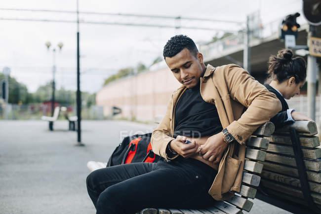 Людина ін'єкційного інсуліну в живіт, сидячи на лавці в платформи Залізничні станції — стокове фото