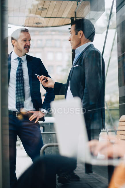 Mature male business colleagues talking while standing at bus shelter seen from glass — Stock Photo