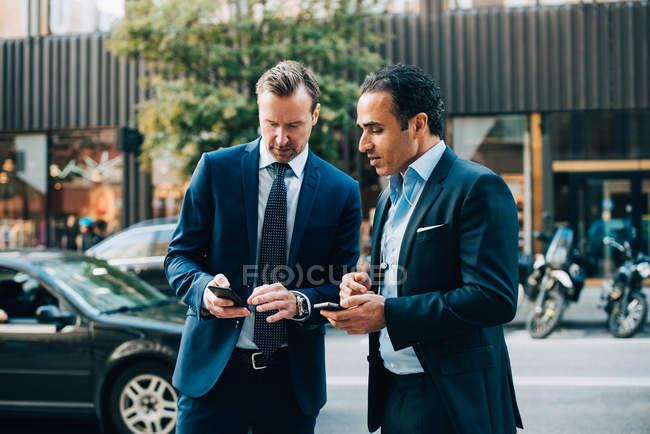 Colegas de trabalho de macho maduro usando telefones móveis em pé na calçada na cidade — Fotografia de Stock
