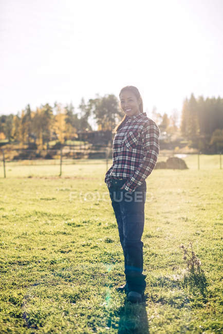 Full length portrait of smiling female farmer standing hands in pockets on field - foto de stock