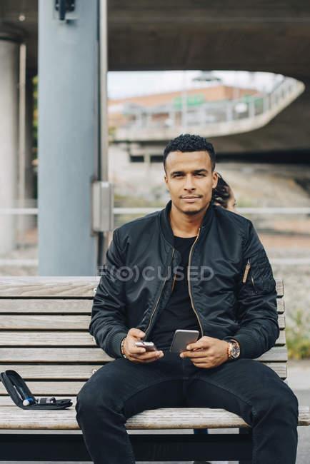 Портрет чоловік тримає глюкометрії і смарт-телефону, сидячи на лавці — стокове фото