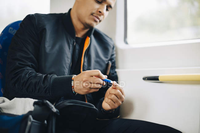 Людина робить аналіз крові, сидячи в поїзді — стокове фото