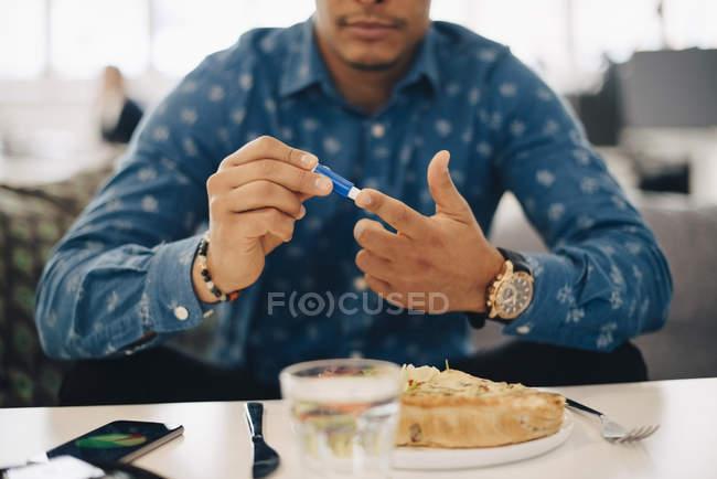 Бізнесмен робить аналіз крові, а їду в таблиці — стокове фото