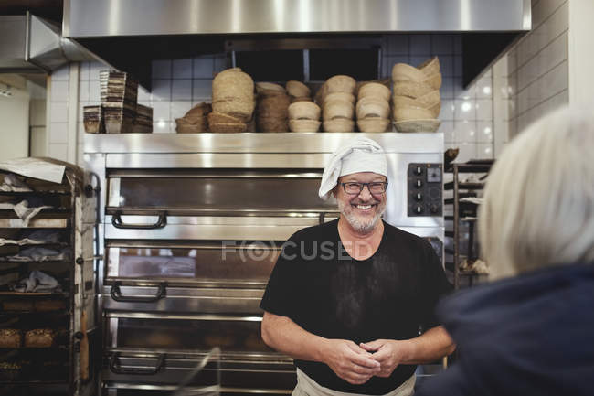 Smiling Senior male baker standing against cooling rack at bakery. - foto de stock