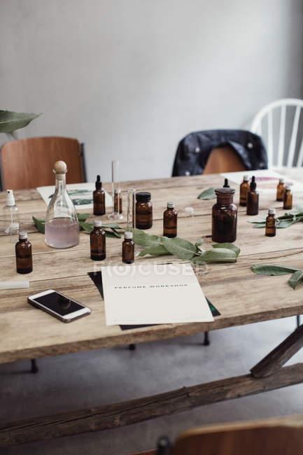Vista de alto ângulo de telefone móvel e folheto por frascos de perfume na mesa de madeira na oficina — Fotografia de Stock