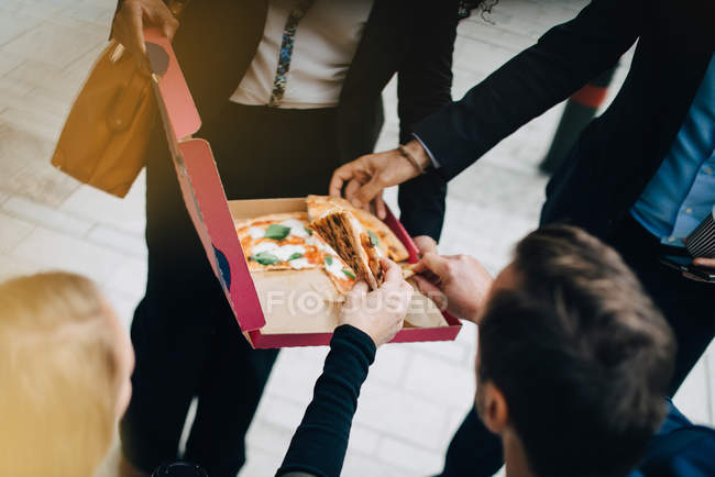 High angle view of business colleagues are eating pizza from box in city — Stock Photo