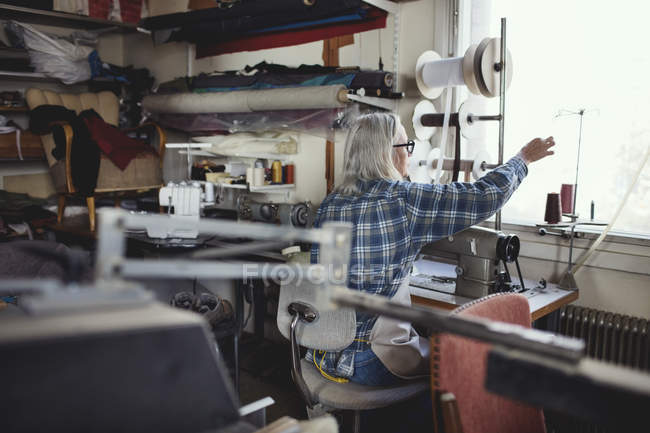 Senior owner using sewing machine at table in workshop — Stock Photo