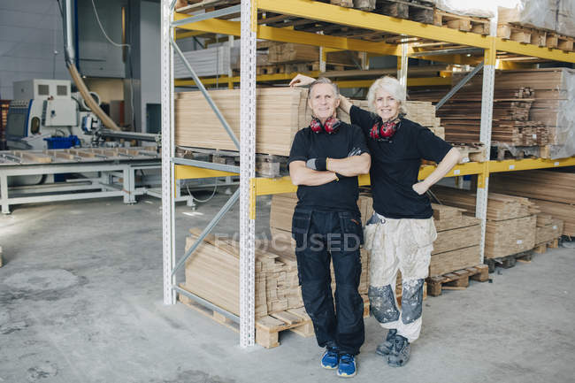 Full length portrait of smiling workers standing by rack in industry — Stock Photo