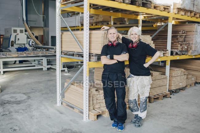 Portrait complet de travailleurs souriants debout par rack dans l'industrie — Photo de stock