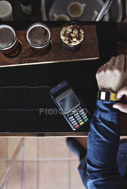 Cropped image of customer doing contactless payment through smart watch by beer glasses at bar counter — Stock Photo