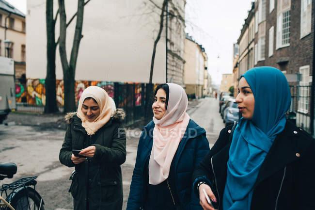 Mujeres amigas musulmanas caminando por la calle en la ciudad - foto de stock