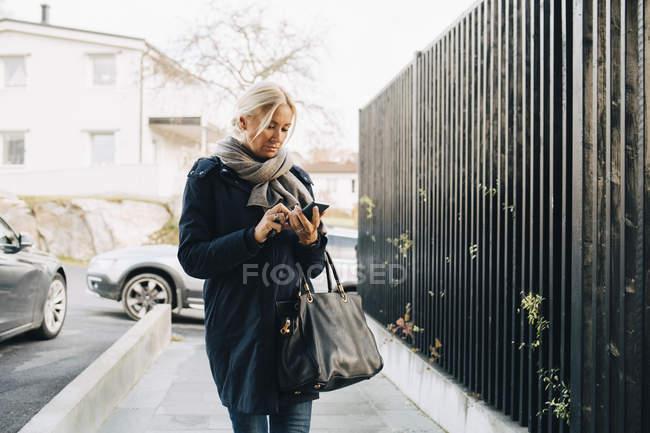 Femme mature utilisant un téléphone intelligent tout en marchant sur le sentier par une clôture — Photo de stock