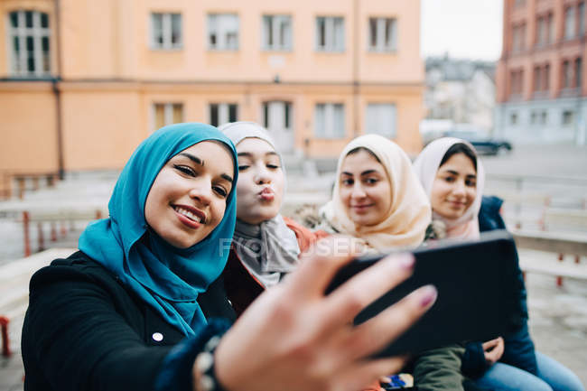 Young woman taking selfie with Muslim female friends in city — Stock Photo