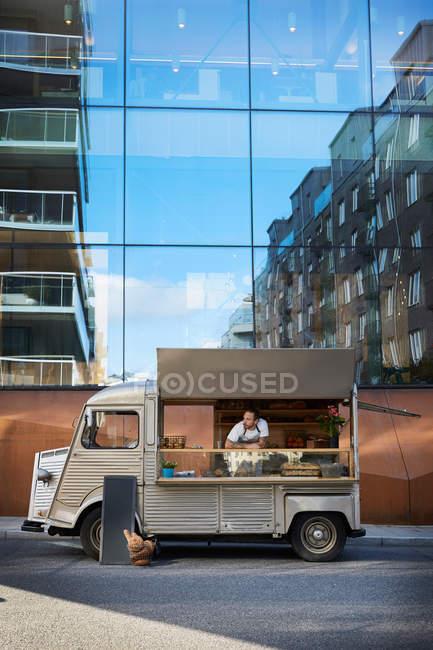 Jeune propriétaire masculin dans un camion de nourriture garé sur la rue de la ville contre le bâtiment en verre — Photo de stock