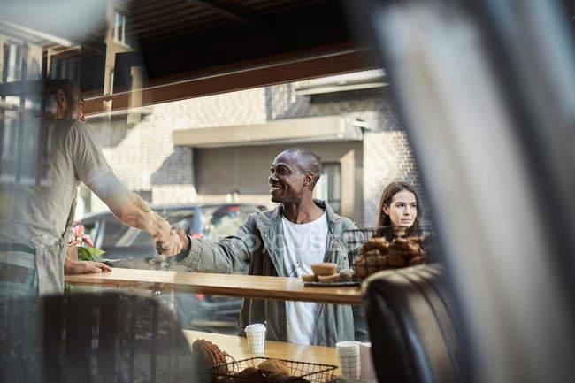 Клиент-мужчина и продавец пожимают друг другу руки у киоска — стоковое фото