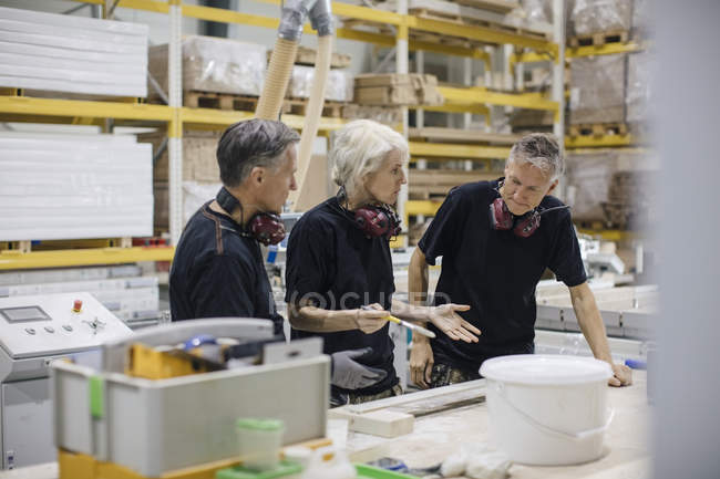 Female workers discussing with colleague while working at industry — Stock Photo