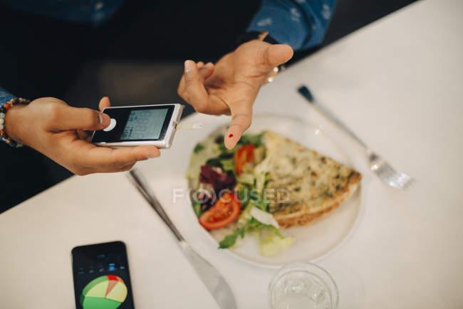 Бізнесмен перевірки рівня цукру крові з glaucometer а їду в таблиці — стокове фото