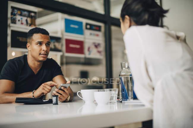 Geschäftsmann im Gespräch mit Kollegen und mit Handy beim Blutzuckertest, während er im Büro am Tisch sitzt — Stockfoto