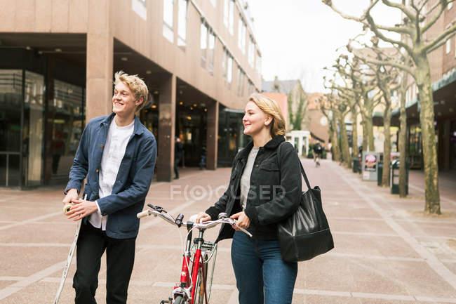 Sorrindo jovem casal viajando com skate e bicicleta na cidade — Fotografia de Stock