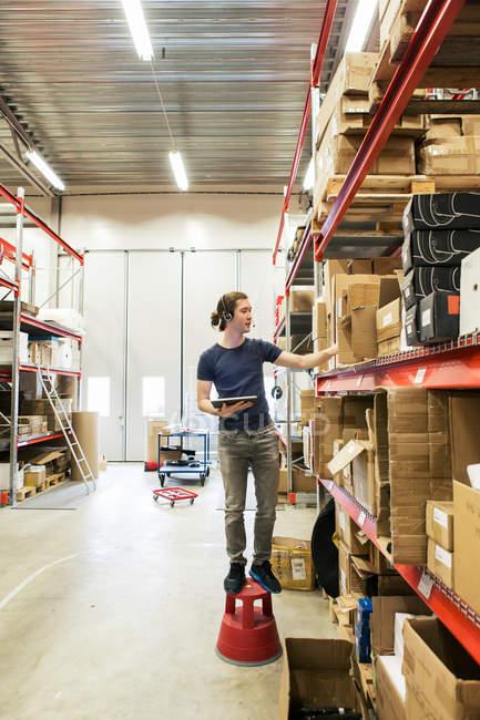Ручний працівник аналізує коробки при використанні цифрового планшета в магазині дистрибуції. — стокове фото