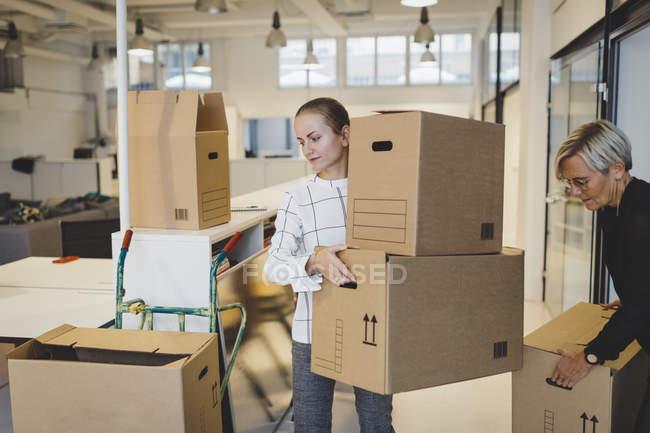 Mujeres de negocios que trasladan cajas de cartón a nuevas oficinas - foto de stock