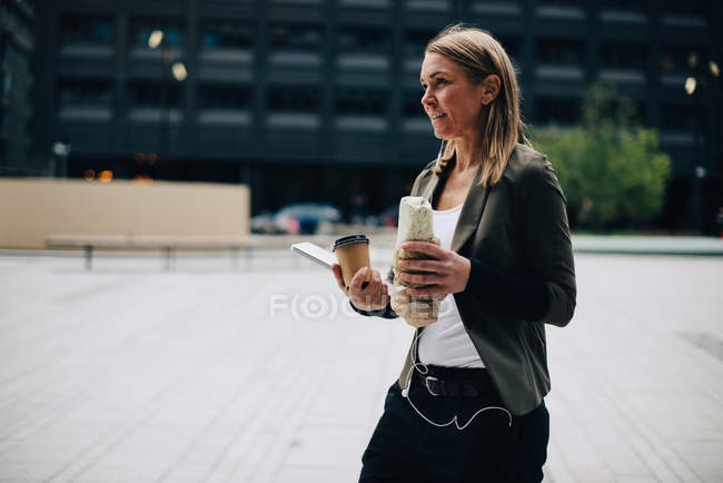 Mature businesswoman carrying food and drink with laptop while walking on footpath in city — Stock Photo
