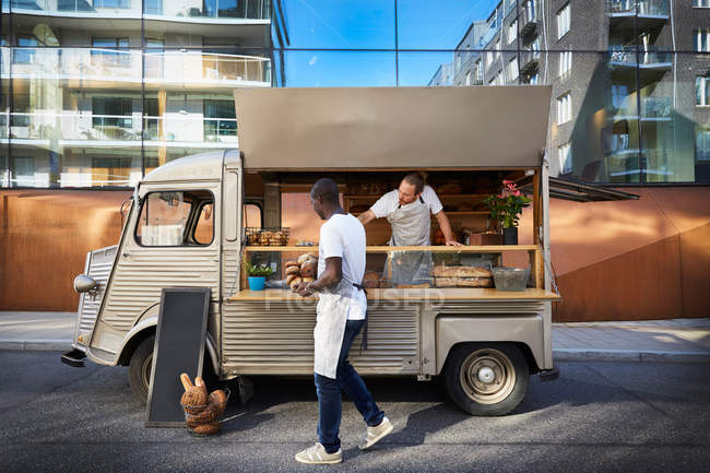 Male owners working at food truck parked on city street — Stock Photo