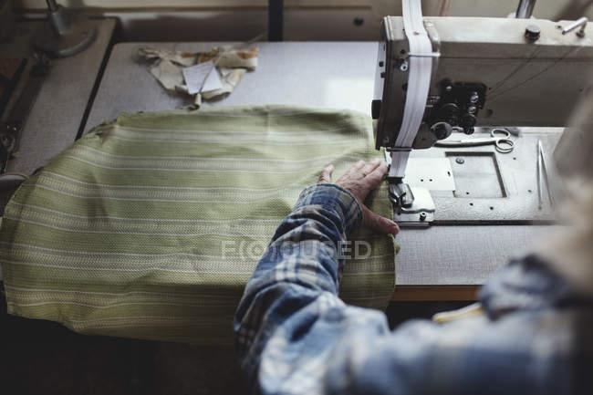 Geschnittenes Bild eines Handwerkers, der in der Werkstatt grünen Stoff auf Maschine näht — Stockfoto