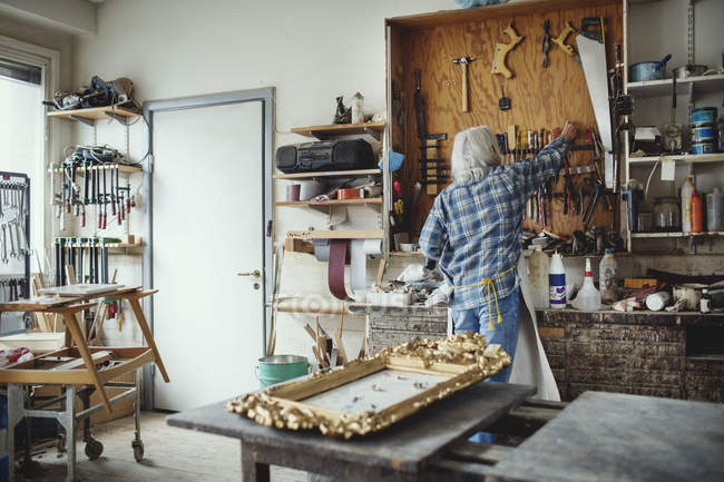 Rear view of senior owner using tools while working at workshop — Stock Photo
