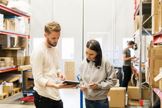 Coworkers looking at digital tablet while planning in distribution warehouse — Stock Photo