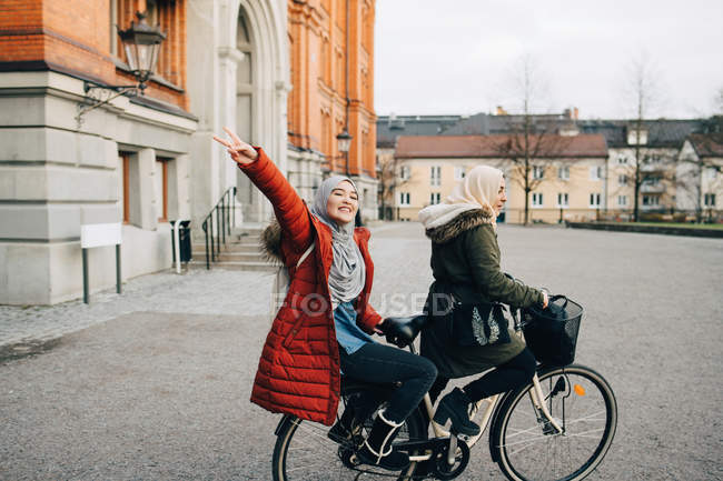 Portrait of happy young woman showing peace sign sitting behind friend on bicycle in city — Stock Photo