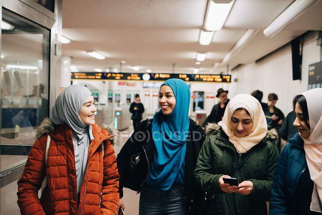 Smiling Muslim female friends standing at subway station — Stock Photo