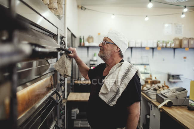 Senior baker standing by oven at bakery — Stock Photo