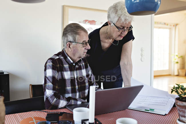 Senior couple with laptop at and financial bills at dining table — Stock Photo