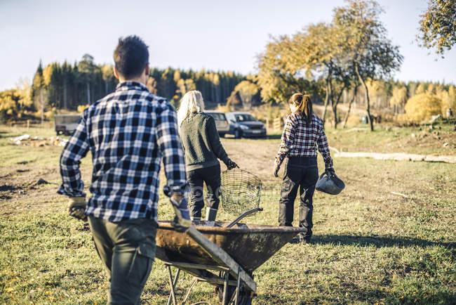 Rear view of male farmer pushing wheelbarrow while following friends at farm — Foto stock