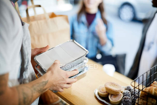 Midsection of salesman holding takeaway packaged food for customers at concession stand — Stock Photo