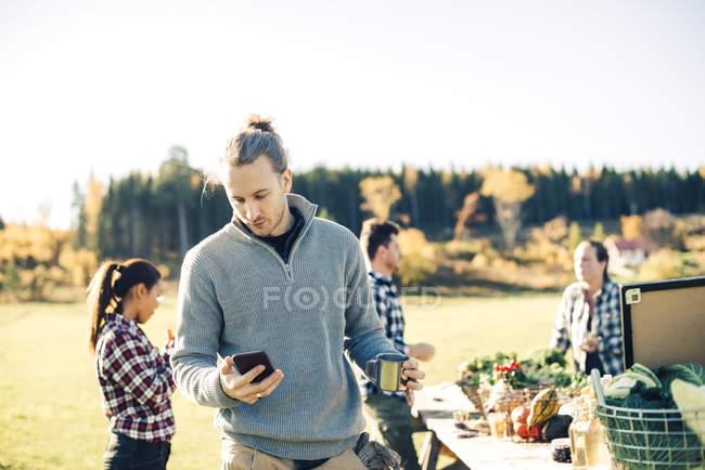Metà adulto maschio agricoltore utilizzando il telefono cellulare mentre tenendo tazza di caffè con gli amici in background — Foto stock