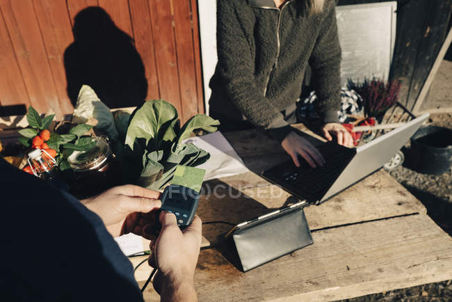 Customer paying with credit card while farmer using laptop at market — Stockfoto