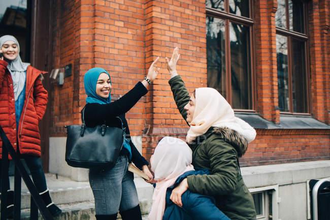 Felices amigas musulmanas dando choca contra la construcción - foto de stock