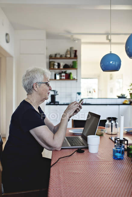 Side view of retired senior woman using smart phone while sitting with laptop at dining table — Stock Photo