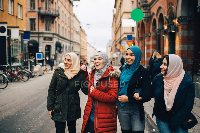 Happy multi-ethnic Muslim female friends standing on street in city — Stock Photo