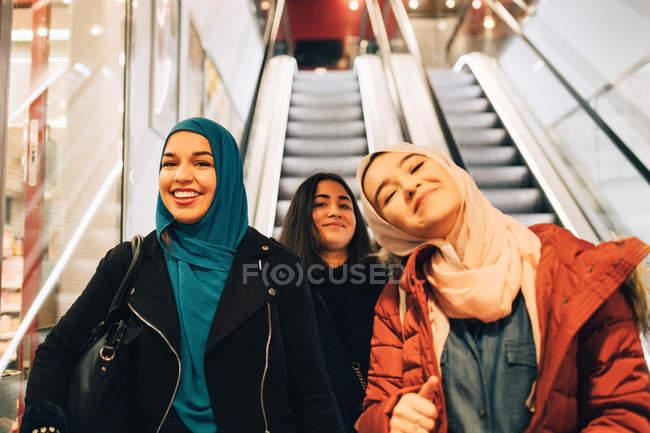 Retrato de amigas felices en escalera mecánica en el centro comercial - foto de stock