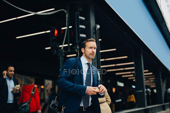 Mature businessman looking away while walking in city — Stock Photo
