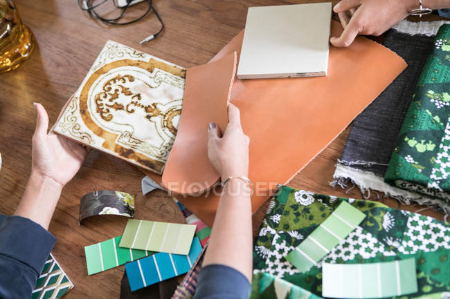 Cropped hands of female design professionals working at table in home office — Stock Photo