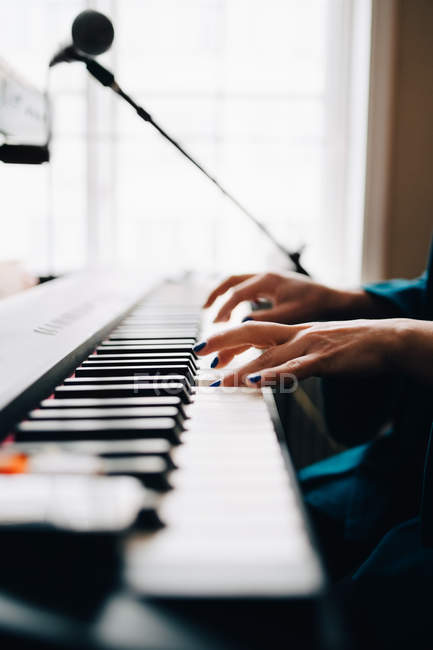 Cropped image of woman playing piano by window at studio — Stock Photo