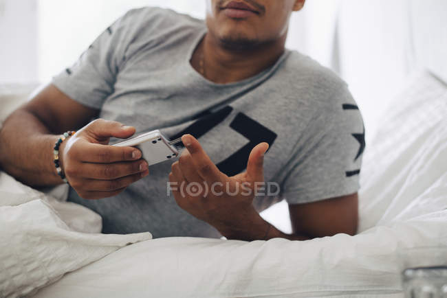 Midsection of man checking blood sugar level on glucometer while lying on bed at home — Stock Photo