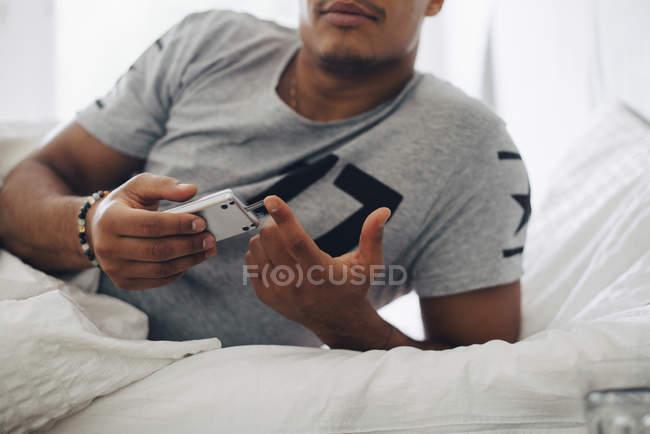 Міделю людина перевірки рівня цукру крові на глюкометрії лежачи на ліжку у себе вдома — стокове фото